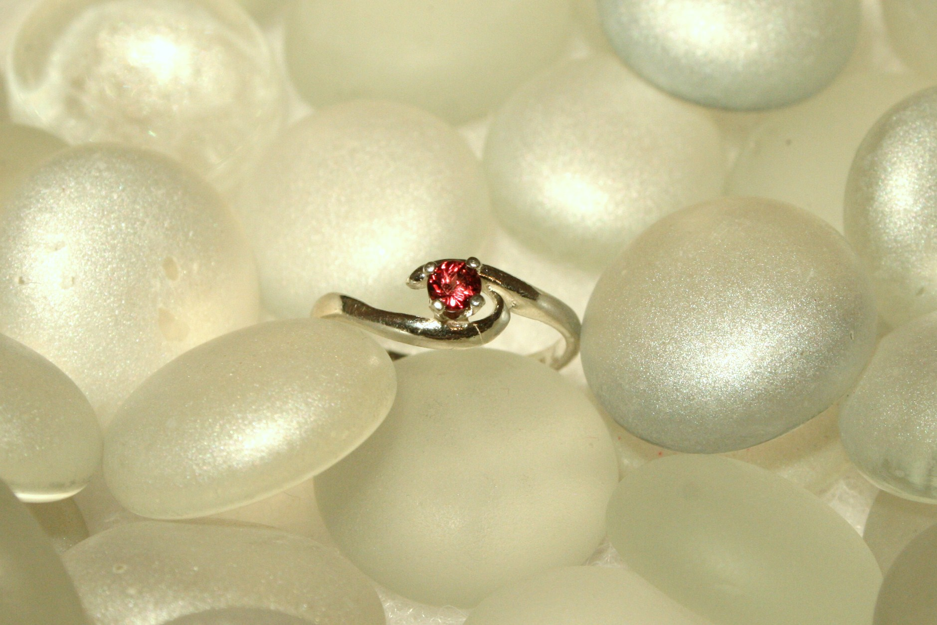 A dainty sterling silver ring set with a beautiful Idaho garnet, The simple band features a slight curve around the garnet. Perfect for any woman and a great choice as a youth ring. Made in Philipsburg, Montana.